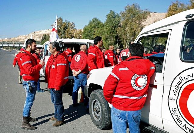 Na snímke členovia sýrskeho arabského Červeného polmesiaca stoja pri konvoji s humanitárnou pomocou, ktorý čaká na predmestí Damasku