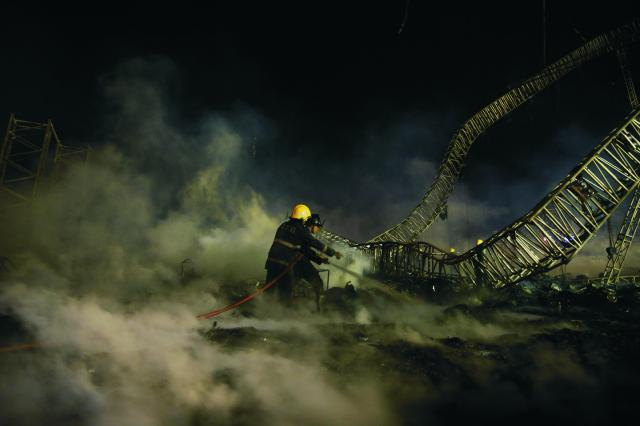 Na snímke indickí požiarníci  uhášajú zvyšky po mohutnom požiari
