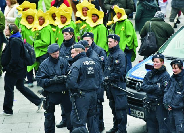 Policajti hliadkujú pred hlavnou železničnou stanicou účastníka počas začiatku pouličného karnevalu v Kolíne nad Rýnom