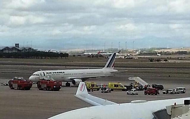 Na snímke hasičské autá a sanitky stoja pri lietadle francúzskych aerolínii Air France so 163 ľudmi na palube na letisku v Madride