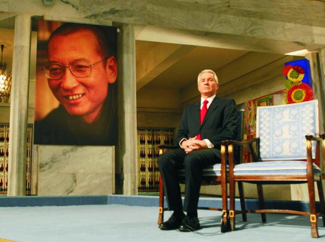 Na snímke Thorbjörn Jagland sedí vedľa prázdneho kresla vyhradeného laureátovi  Nobelovej ceny za mier Liou Siao-poovi (na portréte v pozadí)