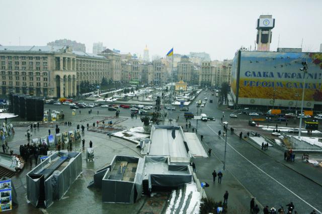 Autá jazdia po Námestí nezávislosti, uprostred v pozadí je ukrajinská vlajka, po protivládnych protestoch v Kyjeve. Vpravo je obrovský transparent s nápisom Sláva Ukrajine! Sláva hrdinom! Takzvanou nebeskou stovkou Ukrajinci v Kyjeve pomenuvávajú obete, ktoré zahynuli počas protivládnych protestov v rokoch 2013 - 2014