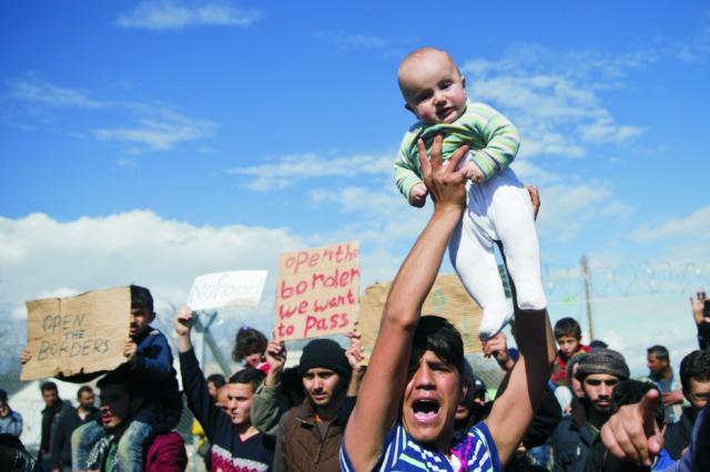 Uviaznutí utečenci a migranti protestujú za opätovné otvorenie grécko-macedónskych hraníc v severogréckej dedine Idomeni 27. februára 2016. Irackí a sýrski migranti, ktorí uviazli na grécko-macedónskej hranici, demonštrujú dnes pokojným spôsobom za jej opätovné otvorenie, aby sa mohli dostať ďalej do Európy po tzv. balkánskej trase