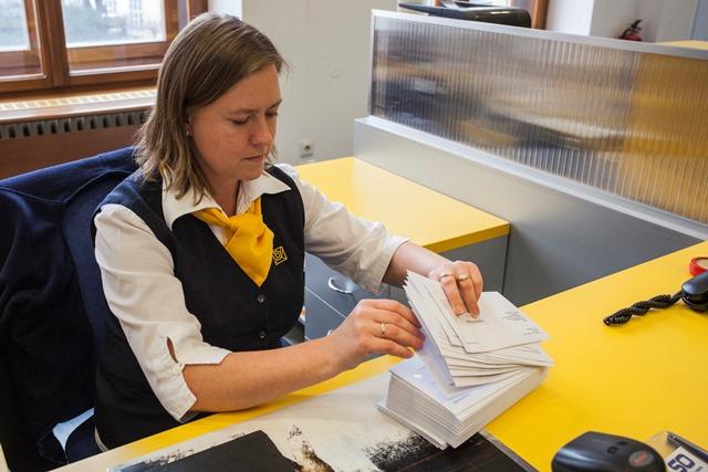 Na snímke pracovníčka pošty preberá listové zásielky s vratkami za plyn