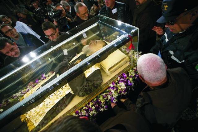 Ľudia stoja okolo boxu s pozostatkami svätca  Pia z Pietrelciny (1887-1968), ktoré previezli za mimoriadnych bezpečnostných opatrení z juhotalianskeho San Giovanni Rotondo do Ríma, konkrétne do tamojšej baziliky San Lorenzo fuori le Mura 3. februára 2016