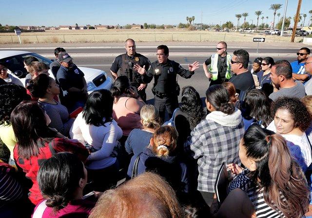 Na snímke policajti informujú rodičov čakajúcich pred strednou školou, kde sa odohrala streľba