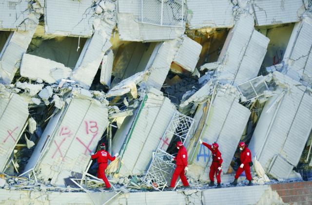 Záchranári prehľadávajú ruiny zrútenej budovy po zemetrasení 8. februára 2016 v Tchaj-nane