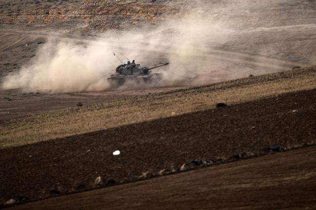 Turecký tank jazdí na kopci s výhľadom na sýrske mesto Kobané. Ilustračné foto