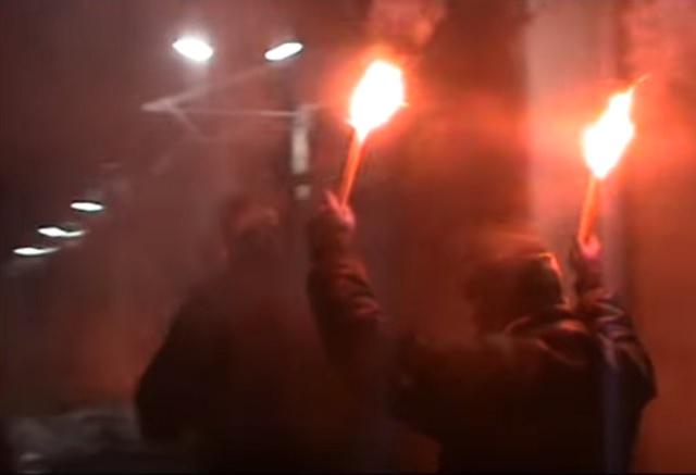Na snímke z videa muž drží v rukách dve zapálené dymovnice