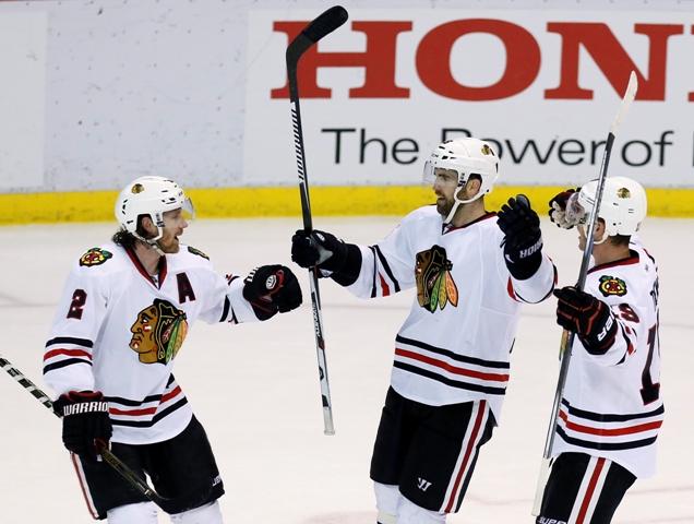 Hokejisti Chicaga Blackhawks Andrew Ladd (uprostred) sa teší po strelení gólu so spoluhráčmi Duncanom Keithom (vľavo) a   Jonathanom Toewsom (vpravo) v zápase zámorskej hokejovej NHL Detroit Red Wings - Chicago Blackhawks