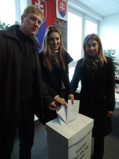 Na snímke vpravo 18-ročná Paulína Janíková, ktorá patrí medzi 167 prvovoličov v okresnom meste, vhadzuje spolu s rodičmi obálky do volebnej urny vo volebnej miestnosti vo voľbách do Národnej rady SR v Malackách