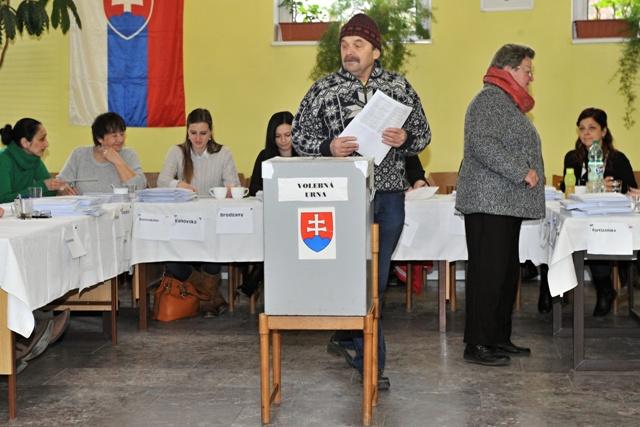 Na snímke volič s hlasovacími lístkami stojí pred volebnou urnou vo voľbách do Národnej rady SR v Turanoch, 5. marca 2016