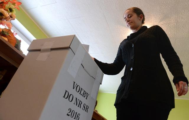 Na snímke volička vhadzuje obálku do volebnej urny vo voľbách do Národnej rady SR  v obci Slanská Huta