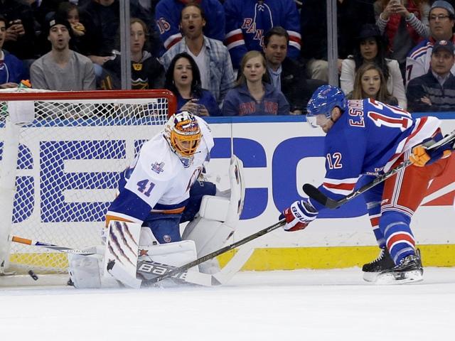 Na snímke vpravo útočník Rangers Eric Staal strieľa gól slovenskému brankárovi Islanders Jaroslavovi Halákovi v zápase hokejovej NHL New York Rangers - New York Islanders