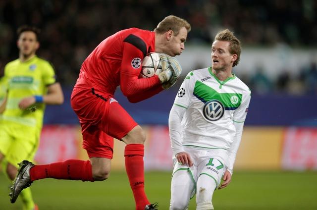Futbalista Wolfsburgu Andre Schürrle (vpravo) a brankár Gentu Matz Sels počas odvetného osemfinálového zápasu futbalovej Ligy majstrov VfL Wolfsburg - KAA Gent