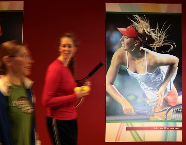 Študentky tenisovej akadémie kráčajú okolo plagátu s podobizňou ruskej tenistky Marie Šarapovovej, ktorý visí na stene v priestoroch tenisovej akadémie v ruskom meste Kazaň