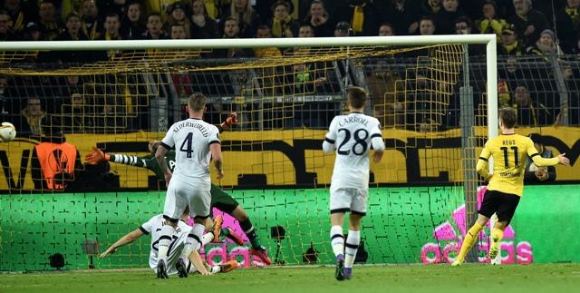 Na snímke vpravo hráč Borussie Marco Reus strieľa tretí gól Dortmundu v prvom zápase osemfinále Európskej ligy vo futbale Borussia Dortmund - Tottenham Hotspur