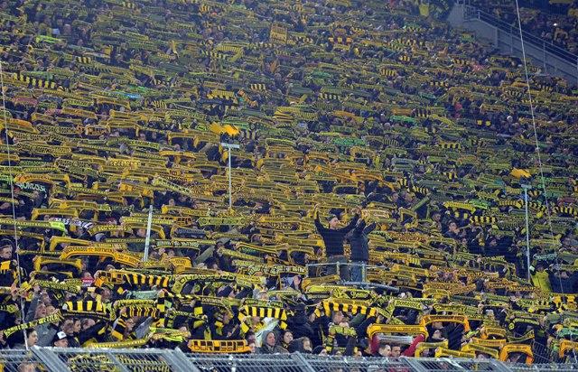 Futbaloví fanúšikovia Borussie Dortmund spievajú pieseň na južnej tribúne štadióna na počesť fanúšika, ktorý dostal v hľadisku infarkt a na mieste zomrel počas zápasu 26. kola nemeckej Bundesligy Borussia Dortmund - FSV Mainz 05 v Dortmunde