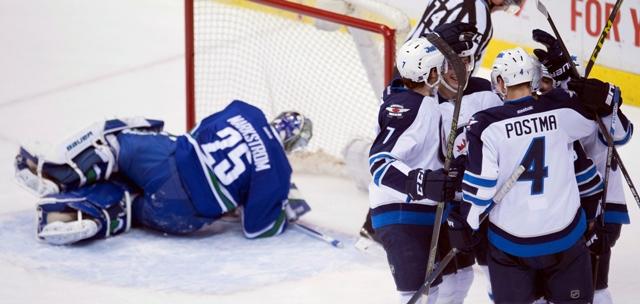 Hokejista Winnipegu Jets Slovák Marko Daňo (uprostred) sa teší so spoluhráčmi po strelení gólu za chrbát brankára Vancouveru Canucks Jacoba Markströma v zápase zámorskej hokejovej NHL Vancouver Canucks - Winnipeg Jets vo Vancouveri