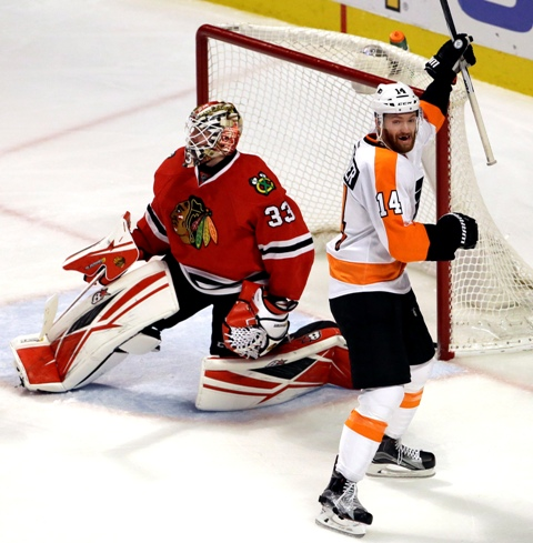 Na snímke vpravo hráč Flyers Sean Couturier oslavuje gól, vľavo prekonaný brankár Blackhawks Scott Darling v zápase hokejovej NHL Chicago Blackhawks - Philadelphia Flyers