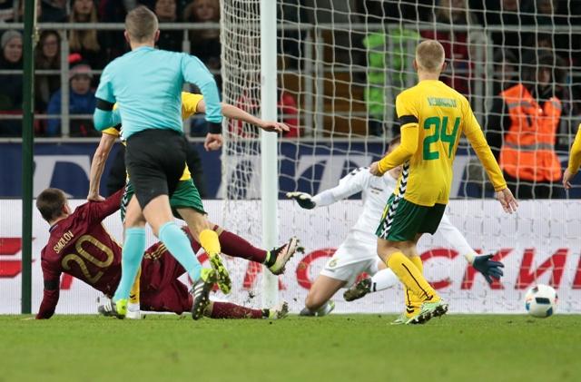 Ruský hráč Fjodor Smolov (vľavo) skóruje cez litovského brankára Vjtautasa Cerniauskasa v prípravnom futbalovom zápase Rusko - Litva