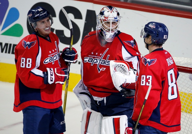 Hokejisti Washingtonu Capitals  brankár Braden Holtby (uprostred), obranca Nate Schmidt (vľavo) a Jay Beagle (vpravo) sa tešia po výhre 4:1 v zápase zámorskej hokejovej NHL