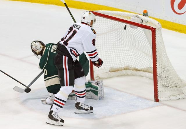 Slovenský hokejista Marián Hossa z Chicaga Blackhawks prekonáva brankára Minnesoty Wild Devana Dubnyka počas zápasu zámorskej NHL