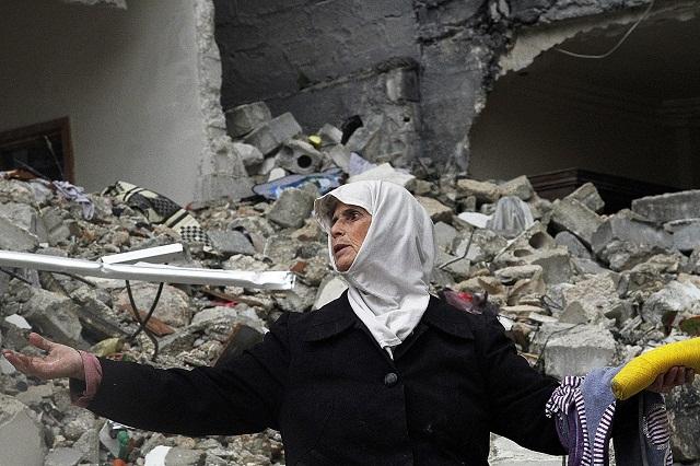 Sýrčanka smúti nad ruinami svojho domu, ktorý bol zničený pri leteckých náletoch