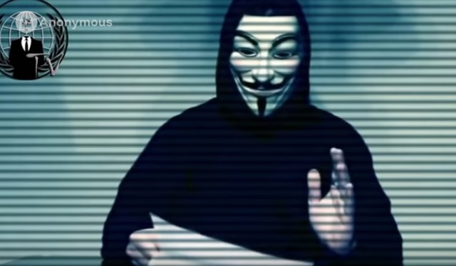 Na snímke  z videa Anonymus muž v maske číta informácie o prezidentskom kandidátovi Donaldovi Trumpovi