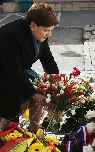 Na snímke poľská premiérka Beata Szydlová kladie kyticu tulipánov vo farbách poľskej trikolóry pred budovou belgického veľvyslanectva vo Varšave