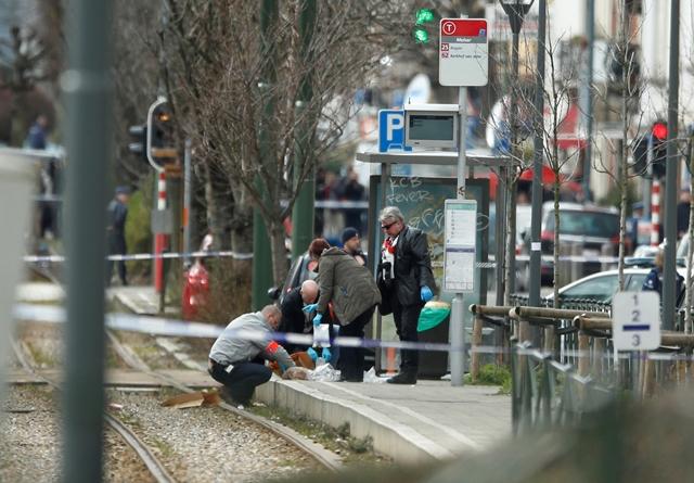 Na snímke policajní vyšetrovatelia zaisťujú stopy na električkovej zastávke počas policajnej akcie v belgickej štvrti Schaerbeek