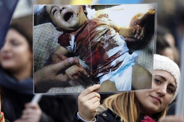 Ilustračná snímka. Protestujúca drží fotografiu raneného sýrskeho dieťaťa