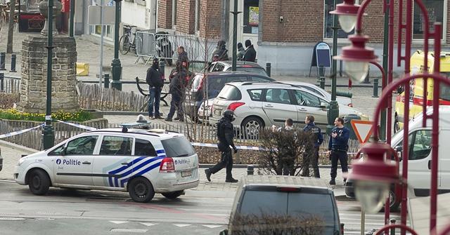 Na snímke policajti zasahujú počas razie v Bruseli