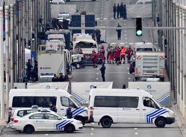 Na snímke policajti a záchranári pred stanicou metra  Maelbeek v Bruseli