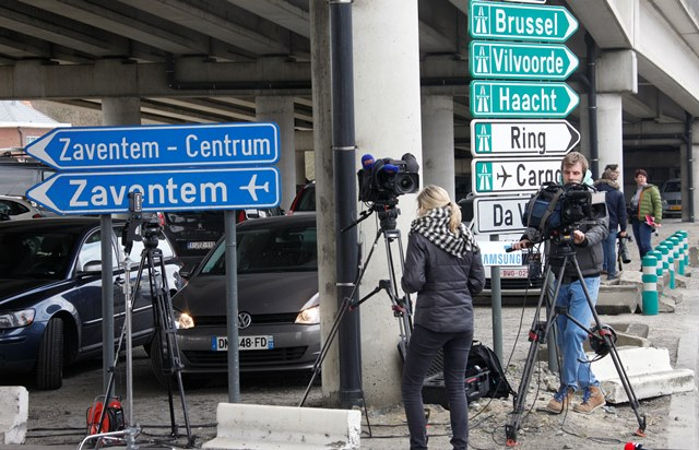 Na snímke novinári sú pred bruselským letiskom, Zaventem po dvoch explóziách, ktoré otriasli odletovou halou medzinárodného letiska