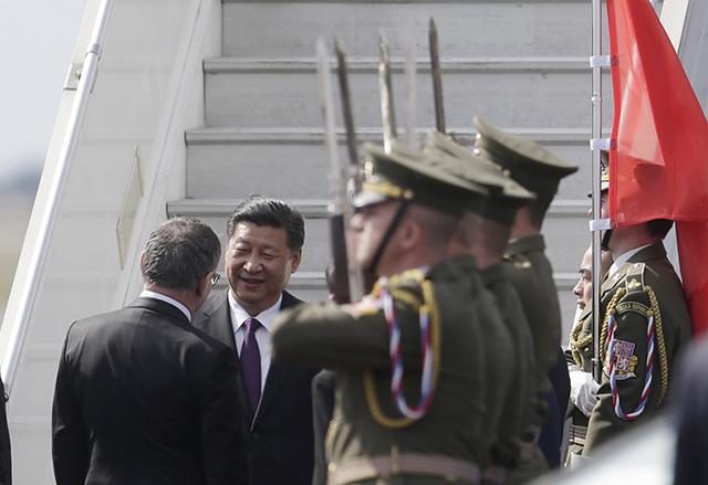 Český minister zahraničných vecí Lubomír Zaorálek (vľavo) víta čínskeho prezidenta Si Ťin-pchinga (vpravo) pri vystupovaní z lietadla po jeho prílete na letisko v Prahe