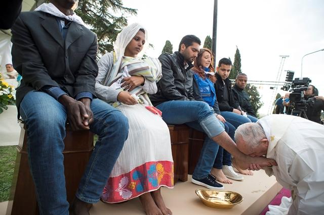 Na snímke pápež František bozkáva nohu žiadateľa o azyl počas rituálu umývania nôh v utečeneckom centre v meste Castelnuovo di Porto