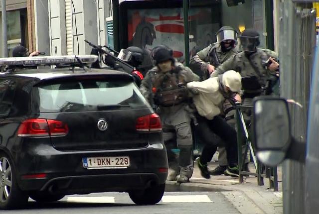Na snímke zo záznamu televízie VTM príslušníci špeciálnej jednotky vedú muža do policajného auta počas policajnej akcie