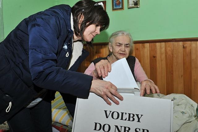 Na snímke členka okrskovej volebnej komisie Mária Walderová (vľavo) a Terézia Bednárová, ktorá vhadzuje obálku do prenosnej volebnej urny vo voľbách do Národnej rady SR v Terchovej, 5. marca 2016