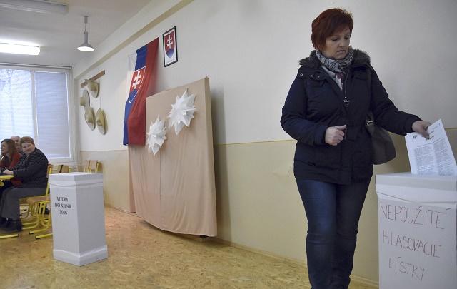 Volička vhadzuje nepoužžité hlasovacie lístky do určenej urny