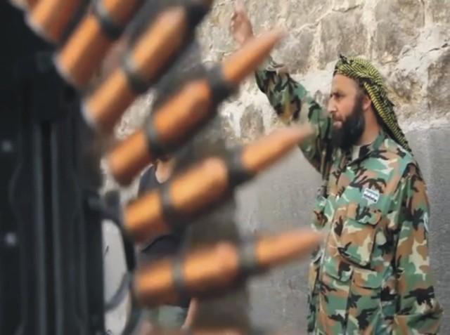 Na archívnej snímke z videa príslušník Slobodnej sýrskej armády gestikuluje počas bojov so sýrskymi vládnymi silami v sýrskom meste Aleppo