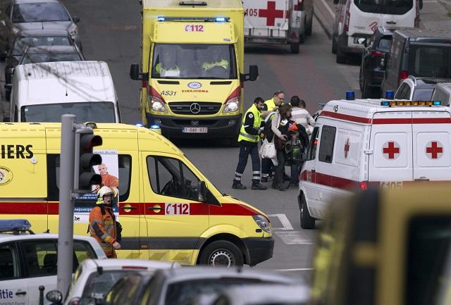 Na snímke záchranári evakuujú zranenú ženu do sanitky po výbuchu v stanici metra v Bruseli