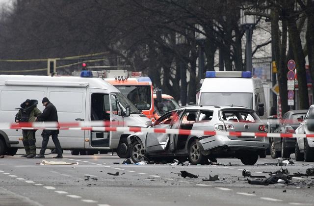 Špecialisti na bomby v ochranných oblekoch zasahujú na mieste explózie nálože umiestnenej v aute na ulici v Berlíne 15. marca 2016