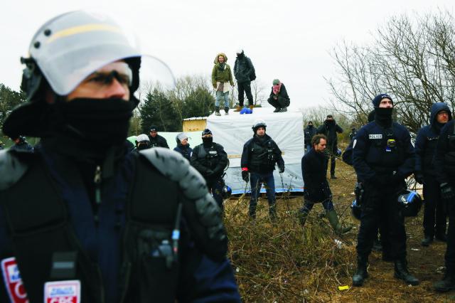 Policajti obklopujú migrantov a aktivistov stojacich na streche príbytkov v stanovom tábore pri francúzskom Calais 1. marca 2016 pred jeho zbúraním. Na predmestí Calais sa usadilo niekoľko tisícok afrických utečencov zo Stredomoria. Francúzske úrady začali odstraňovať rozsiahly tábor migrantov v meste Calais, kde žijú tisíce ľudí, dúfajúcich, že sa im podarí dostať do Británie za lepším životom