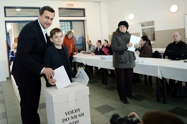 Predseda Slovenskej národnej strany (SNS) Andrej Danko so synom Adamom vhadzuje obálku do volebnej urny vo voľbách do Národnej rady SR v Miloslavove