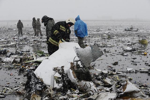 Na snímke pracovník  ruského ministerstva pre mimoriadne situácie si prezerá úlomky lietadla Boeing 737-800 nízkonákladovej leteckej spoločnosti FlyDubai, ktoré sa zrútilo vo vzdialenosti približne 250 metrov od prahu pristávacej dráhy na letisku v Rostove na Done