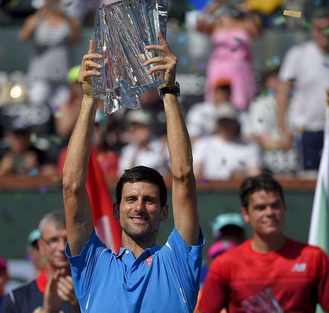 Srbský tenista Novak Djokovič zdvíha trofej po víťazstve nad Kanaďanom Milošom Raoničom (vpravo) vo finále mužskej dvojhry na turnaji ATP v americkom Indian Wells 20. marca 2016