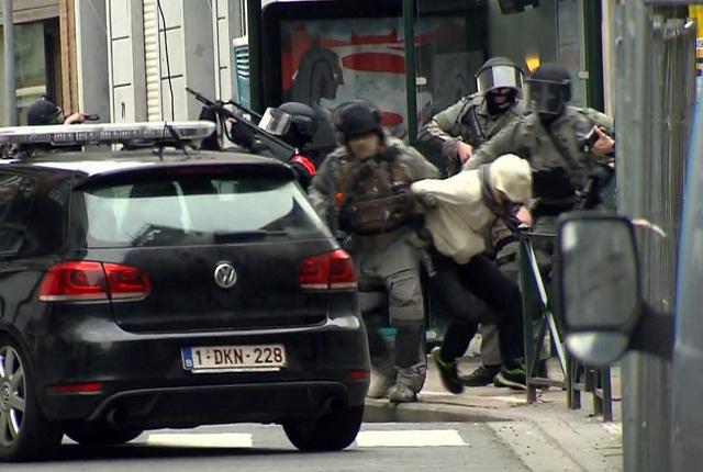 Na snímke zo záznamu televízie VTM príslušníci špeciálnej jednotky vedú muža do policajného auta počas policajnej akcie v Molenbeeku 18. marca 2016. Hlavný strojca parížskych teroristických útokov Salah Abdeslam bol počas protiteroristickej operácie zranený na nohe a následne zatknutý. Pri prestrelke bol zranený belgický novinár
