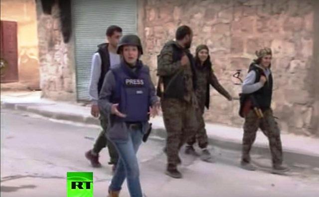 Reportáž o tom pripravila novinárka televíznej stanice Russian Today Lizie Phelan Reportáž o  bojoch v Sýrii  pripravila novinárka televíznej stanice Russian Today Lizie Phelan ( na snímke v popredí)