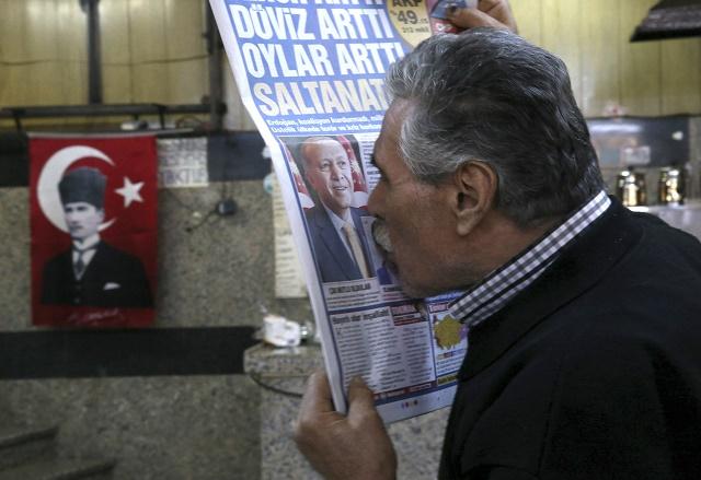 Na snímke Turek bozkáva portrét tureckého prezidenta Erdogana na titulnej strane novín